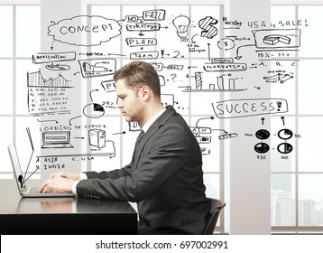 Side view of handsome young european businessman in suit using laptop computer while sitting at office desk in concrete interior with city view and business sketch. Startup concept. 3D Rendering