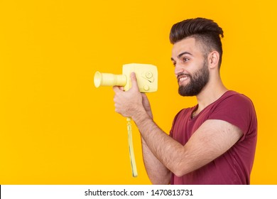 Side view of a handsome young male hipster with a beard shoots objects on a vintage video camera on a yellow background with copy space. Concept of video