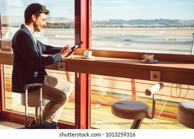 Side view of handsome young man using tablet while drinking coffee in cafe.