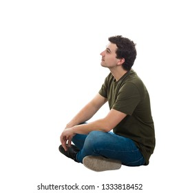 Side view handsome young man wearing casual jeans and t-shirt, sitting relaxed on the floor with crossed legs, looking thoughtful away isolated over white background with copy space.