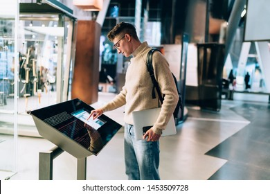 Side view of handsome young man in glasses and with backpack standing with gadgets in hands while using information panel in shopping centre