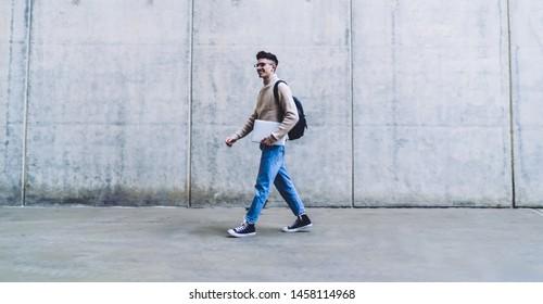 Seitenansicht eines gut aussehenden jungen Mannes in Brillen und Pullover mit Rucksack, der einen weißen Laptop hält, während er in der Stadt lächelt und auf graue Mauer geht