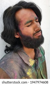 Side view of handsome young man covered with multi color holi powder with white wall background, Bearded and long haired Indian guy celebrating Holi festival, Man making sad face with eyes closed