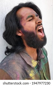 Side view of handsome young man covered with multi color holi powder with white wall background, Bearded and long haired Indian guy celebrating Holi festival, Man opening mouth with eyes closed