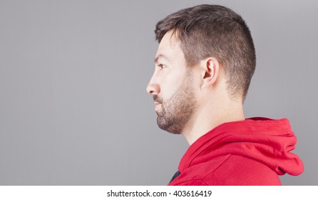 Side view of a handsome young man on grey background