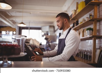 Side view of handsome young waiter using computer at counter in coffee shop