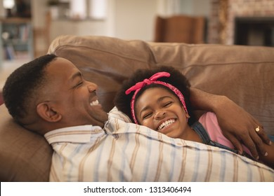 Side view of happy African American father and daughter relaxing on the sofa at home