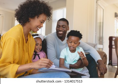 Side view of happy African American parents with their cute children reading storybook on the sofa in a comfortable home