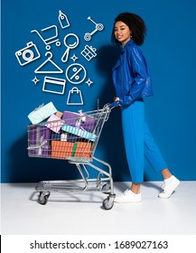 side view of happy african american woman with shopping cart full of gifts on blue background