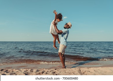 side view of happy african american father playing with cute little daughter on beach