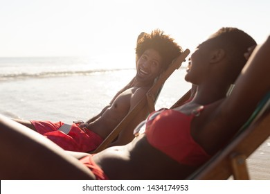 Side view of happy African-american couple interacting with each other while relaxing in a beach chair on the beach