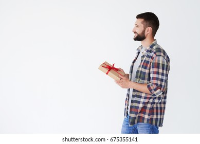 Side view of happy bearded man holding present box over white background. Wearing casual clothes looking at copy space