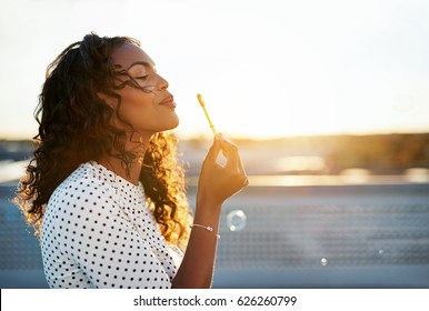 Side view of a happy black woman blowing bubbles against the sunlit sky