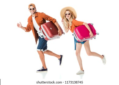 side view of happy couple running with travel bags isolated on white