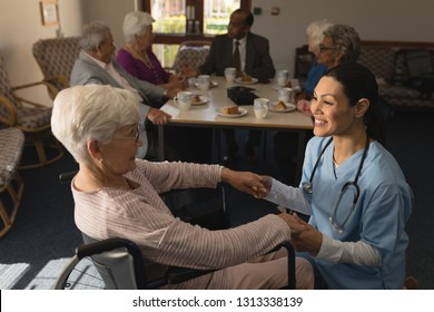Side view of happy female doctor holding hands and talking with disable senior woman at nursing home