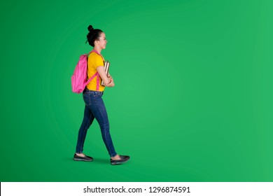 Side view of happy female student carrying books and backpack while walking in the studio with green screen