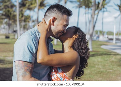 Side view of happy flirting couple of man and black girl standing in tropical park and kissing gently in happiness.