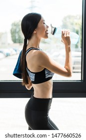 side view of happy girl with closed eyes drinking water while holding sport bottle
