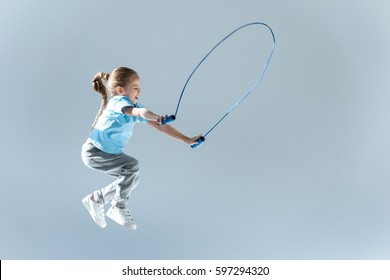 side view of happy girl humping exercising with skipping rope isolated on grey