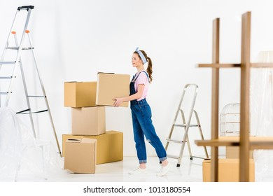 side view of happy girl standing with box
