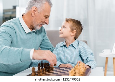 side view of happy grandson and grandfather looking at each other while playing chess at home