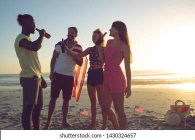 Side view of happy group of diverse friends drinking beer at beach during sunset