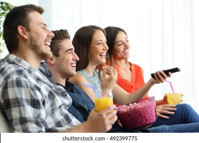 Side view of a happy group of four friends watching and enjoying tv sitting on a sofa in the living room at home