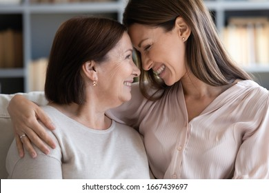 Side view happy grown up daughter embracing shoulders touching foreheads with smiling pleasant middle aged mother, relaxing together on comfortable couch in living room, enjoying free leisure time.