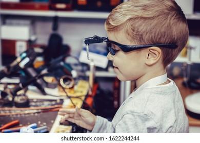 Side view of happy kid with magnifying eyeglasses in engineering workshop.