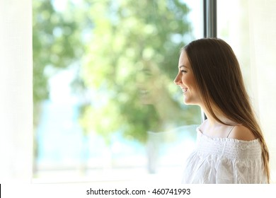 Side view of a happy lady at home looking outdoors through a window of a living room or bedroom with a sunny green background