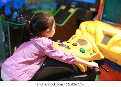 Side view of happy little Asian kid girl playing arcade video game. Motorcycle Racing.