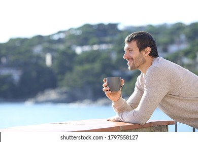 Side view of a happy man contemplating views with coffee cup on a balcony on the beach