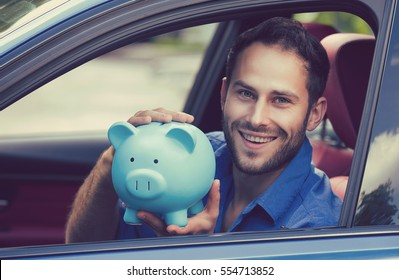 Side view happy man sitting inside his new car holding piggy bank