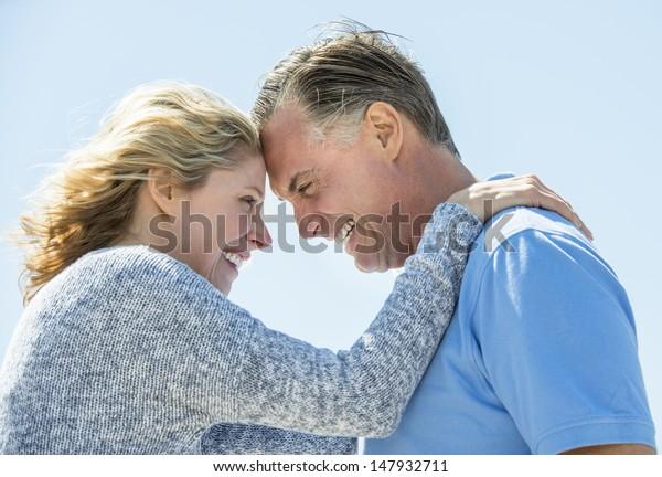 Vista lateral de feliz pareja madura mirándose el uno al otro contra el cielo azul claro