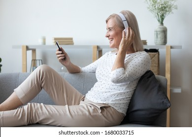 Side view happy middle aged woman enjoying favorite music in wireless headphones, relaxing on comfortable couch at living room. Smiling satisfied female retiree choosing songs of youth in mobile app.