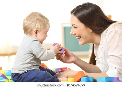 Side view of a happy mother and son playing with toys on the floor