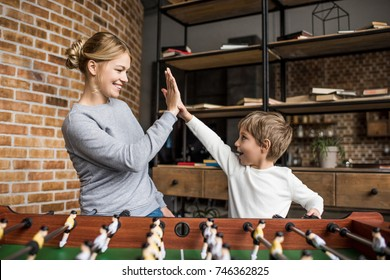 side view of happy mother and son giving high five to each other while playing table football together at home