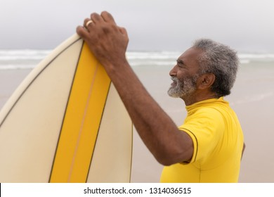 Side view of happy senior male surfer standing with surfboard on the beach