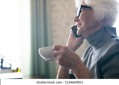 Side view of happy senior woman having a conversation on mobile phone while enjoying a cup of coffee
