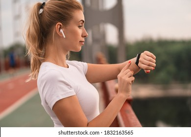 Side view of happy slim woman using smartwatch and listening to music with headphones during workout in the city. Health and sport concept