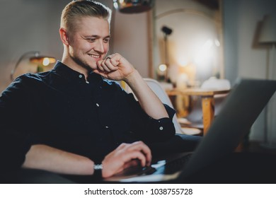 Side view of happy smiling handsome businessman working at night from home, smiling male freelancer working online at vintage loft interior using modern laptop computer