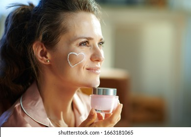 Side view of happy stylish female in pajamas with white facial cream heart on cheek holding pink cosmetic jar at modern home in sunny winter day.