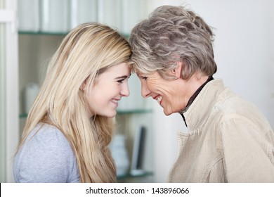 Side view of a happy teenage girl and grandmother looking at each other