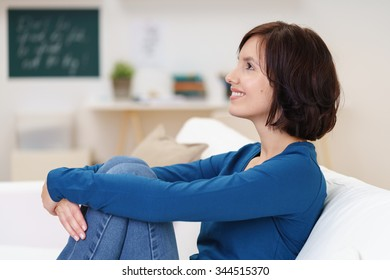 Side View of a Happy Thoughtful Young Woman Sitting on Couch and Embracing her Legs.