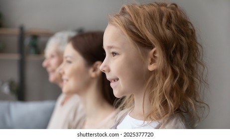 Side view of happy three generations of women look in distance think dream of future together. Smiling teen girl child with young mother and old grandmother show family unity. Offspring concept.