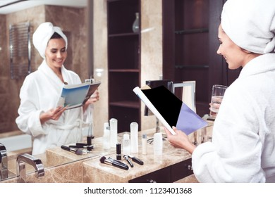 Side view of happy woman in bathrobe standing in front of mirror. She is holding journal and glass of water with smile. Make up and cosmetic tools are scattered nearby. Her reflection is on background