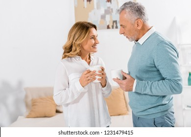 side view of happy woman with coffee cup talking to mature husband at home