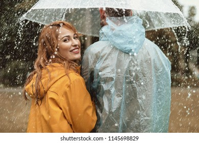 Side view of happy woman strolling with man. They are hiding under umbrella with joy. Smiling female is turning and looking back with content