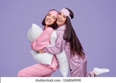 Side view of happy women with pillows smiling and embracing while having fun together during slumber party against violet background