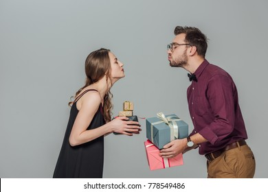side view of happy young couple holding gift boxes and able to kiss isolated on grey